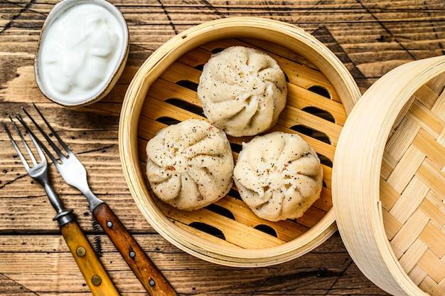 Aziatische gestoomde dumplings manti in een bamboestoomboot.