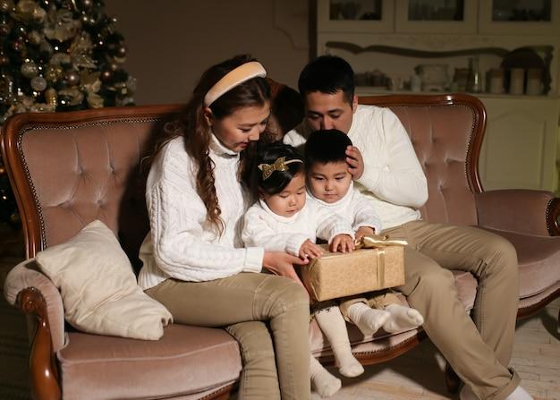 Aziatische gezin met twee kinderen openen geschenken zittend op de bank bij de boom 's nachts thuis