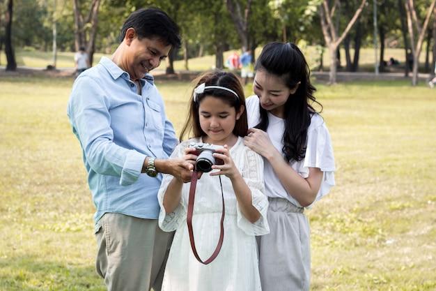 Aziatische gezinnen kijken naar foto's van hun camera's.