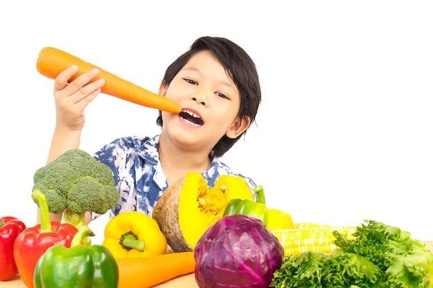 Aziatische gezonde jongen die gelukkige uitdrukking met verscheidenheid verse kleurrijke groente toont