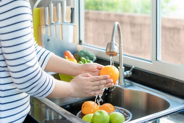 Aziatische gezonde vrouw die een sinaasappel en ander fruit boven gootsteen wast en een groente / fruit met water schoonmaakt om de kans op besmetting covid-19 te elimineren.