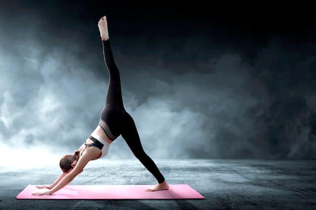 Aziatische gezonde vrouw het praktizeren yoga op het tapijt bij binnen