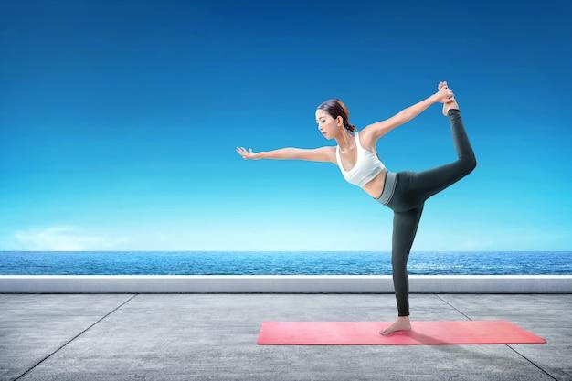 Aziatische gezonde vrouw het praktizeren yoga op het tapijt bij terras