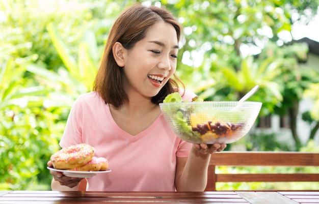 Aziatische gezonde vrouw van middelbare leeftijd zitten en kiezen tussen een donut en een groentesalade