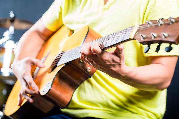 Aziatische gitarist speelmuziek in opnamestudio