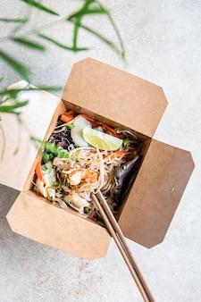 Aziatische glasnoedels met verschillende soorten zeevruchten, groenten en paddenstoelen in een wegwerpdoos