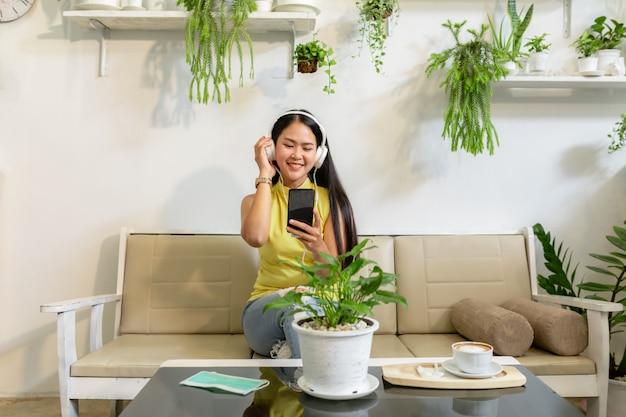 Aziatische glimlachende studente draagt draadloze hoofdtelefoonstudie online met skype leraar in een koffiewinkel,