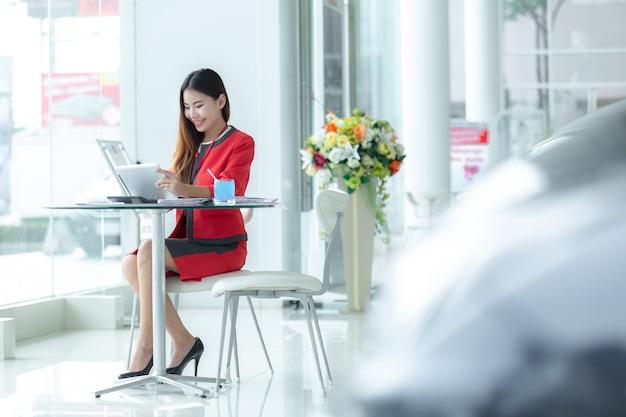 Aziatische glimlachende succesvolle onderneemster in kostuum die op telefoon spreken die tabletzitting van met gebruiken