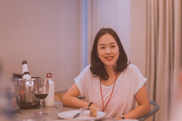 Aziatische glimlachende vrouw die in een ontspannen stemming zit aan de eettafel, vrouwelijk model potrait