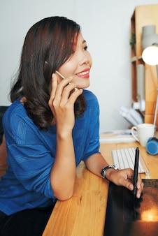 Aziatische grafisch ontwerper die details met klant bespreekt