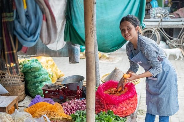 Aziatische groenteman haalt wortelen uit zakken om haar groentekraam op een traditionele markt te tonen