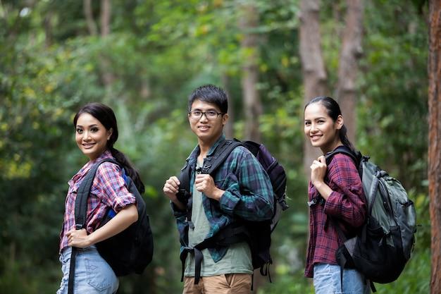 Aziatische groep jongeren wandelen met vrienden rugzakken poseren in het bos