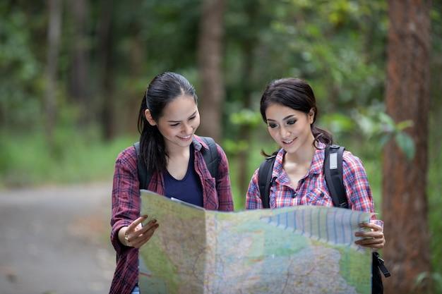 Aziatische groep jongeren wandelen met vrienden rugzakken samen wandelen en kaart kijken