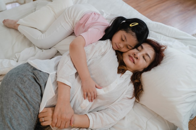 Aziatische grootmoederslaap thuis. hogere chinees, gelukkige oma ontspant met jonge kleindochtermeisje het kussen wang voor wakker het liggen op bed in slaapkamer thuis bij nachtconcept.