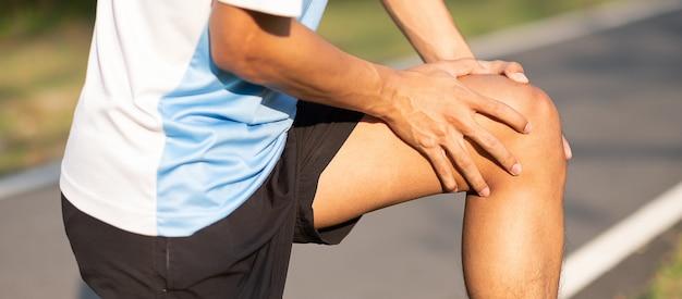 Aziatische hardloper met kniepijn en probleem na hardlopen en lichaamsbeweging buiten