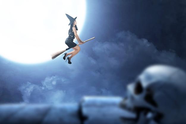 Aziatische heksenvrouw die met hoed op een magische bezemsteel met een volle maanachtergrond vliegen