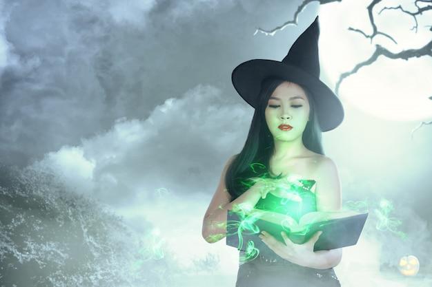 Aziatische heksenvrouw in hoed leert de spreuk van het magische boek