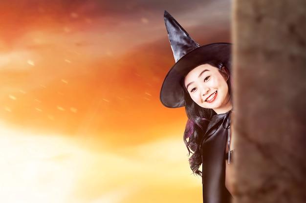 Aziatische heksenvrouw met een hoed die zich met dramatische achtergrond bevindt