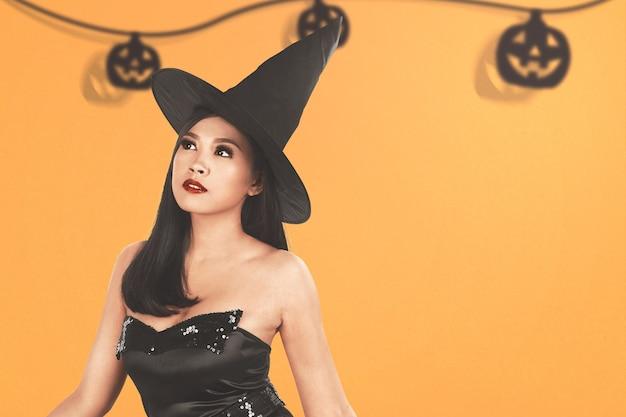 Aziatische heksenvrouw met een hoed die zich met een gekleurde achtergrond bevindt