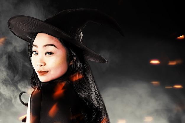 Aziatische heksenvrouw met een hoed die zich met een zwarte achtergrond bevindt