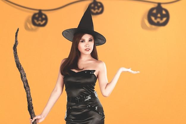 Aziatische heksenvrouw met een hoed en een bezemsteel die zich met een gekleurde achtergrond bevindt