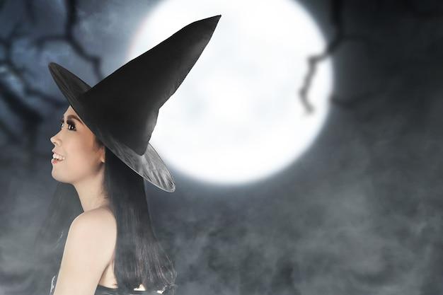 Aziatische heksenvrouw met een mantel die zich met de achtergrond van de nachtscène bevindt