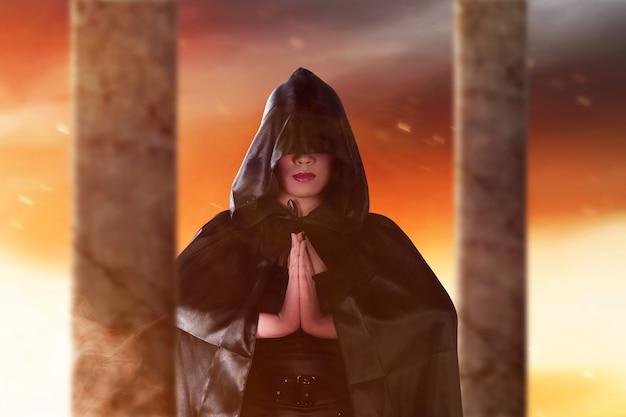 Aziatische heksenvrouw met een mantel die zich met dramatische achtergrond bevindt