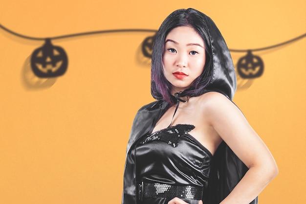 Aziatische heksenvrouw met een mantel die zich met een gekleurde achtergrond bevindt