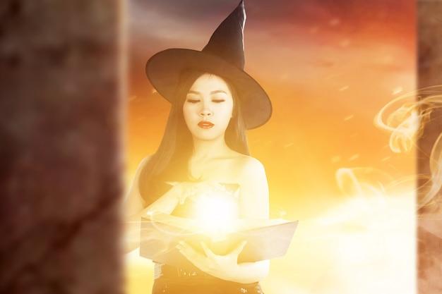 Aziatische heksenvrouw met spreukenboek die magie op haar hand met dramatische achtergrond toont