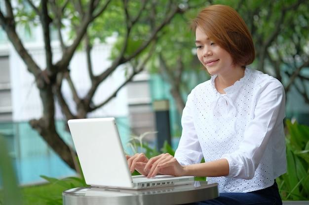 Aziatische het gebruikslaptop van de vrouwenzitting bij park openlucht