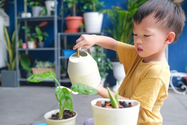 Aziatische het jonge geitje van de peuterjongen het water geven installaties met gieter na thuis het planten van jonge boom in tuin