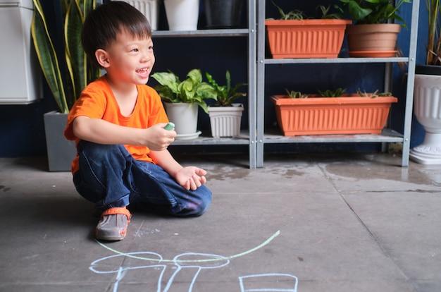 Aziatische het kindtekening van de peuterjongen met kleurkrijtje, weinig jong jong geitjeverblijf die thuis alleen spelen, creatieve vrije tijd voor peuterconcept