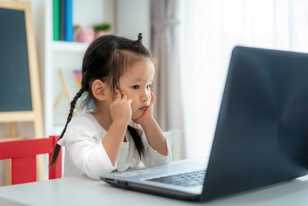 Aziatische het meisjes videoconferentie van de kleuterschoolschool e-leert met leraar op laptop in woonkamer thuis. thuisonderwijs en afstandsonderwijs, online, onderwijs beschermen tegen het covid-19-virus.