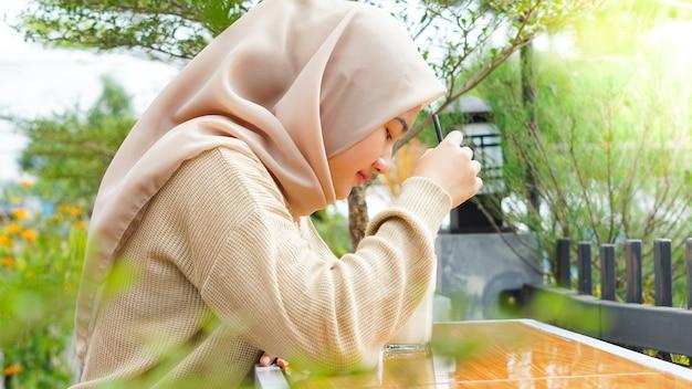 Aziatische hijab vrouw drinken in café