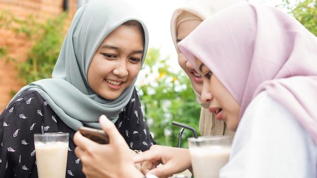 Aziatische hijab vrouw groep smilling in café met vriend