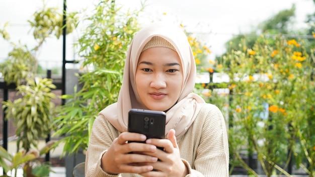Aziatische hijab vrouw speelt telefoon in café