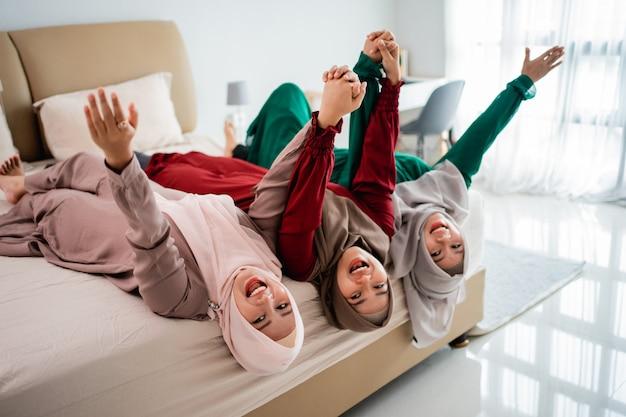 Aziatische hijab-vrouwen en vrienden gingen liggen en hieven hun handen op het bed terwijl ze samen plezier hadden