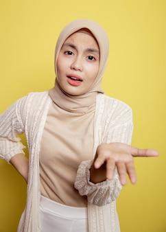 Aziatische hijab-vrouwen praten vragend. verwarren uitdrukking. geïsoleerd op een gele achtergrond