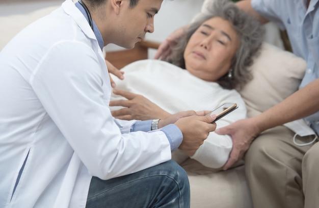 Aziatische hogere bejaarde oude geduldige vrouw die op bank in huis bepaalt dat op resultaat wacht