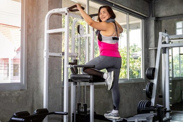 Aziatische hogere dikke vrouw in sportkleding opleiding terug met machine bij gymnastiek.