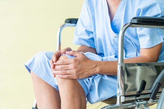 Aziatische hogere geduldige rolstoel met kniepijn