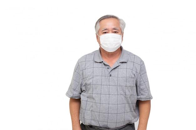 Aziatische hogere mens die een beschermend gezichtsmasker voor besmettelijke ziekte covid-19 draagt die op witte muur wordt geïsoleerd. hygiënisch gezichtsmasker voor veiligheid buiten milieubewustzijn of virusverspreiding concept