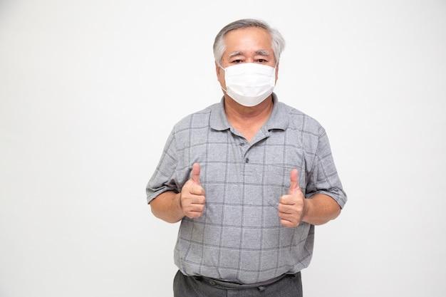 Aziatische hogere mens die een beschermend gezichtsmasker voor plaagcoronavirus of covid-19 besmettelijke ziekte draagt. hygiënisch gezichtsmasker voor veiligheid buiten milieubewustzijn of virusverspreiding concept