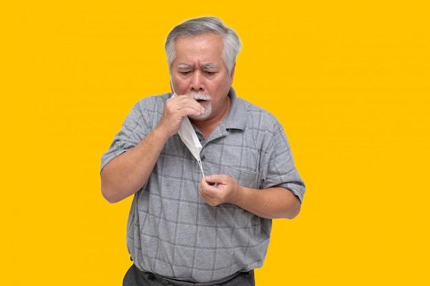 Aziatische hogere mens die een beschermend gezichtsmasker voor plaagcoronavirus of covid-19 besmettelijke ziekte draagt