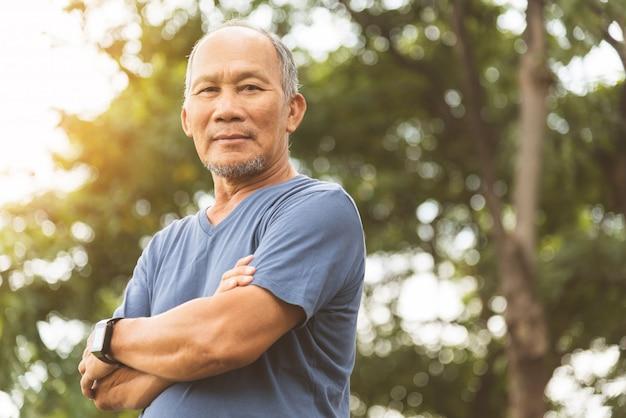 Aziatische hogere mens die in blauw overhemd met gekruiste wapens glimlacht alvorens te oefenen.