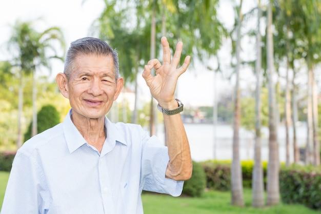 Aziatische hogere mens die op ok teken in het park wijst