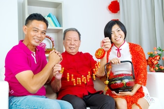 Aziatische hogere mens en kinderen die Chinees nieuw jaar vieren
