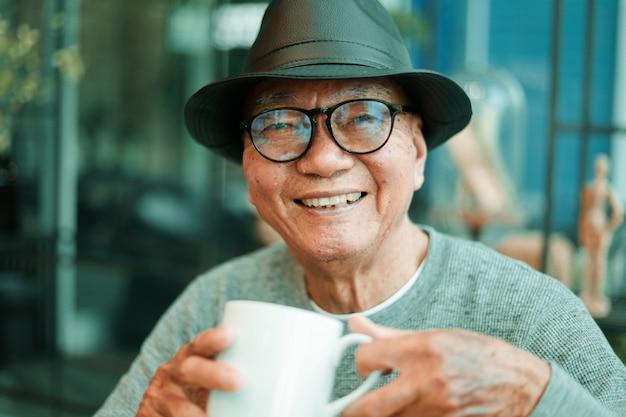 Aziatische hogere mens het drinken koffie in de koffie van de koffiewinkel