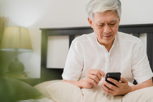Aziatische hogere mensen die mobiele telefoon thuis met behulp van. aziatische hogere chinese mannelijke onderzoeksinformatie over hoe te aan goede gezondheid op internet terwijl thuis het liggen op bed in slaapkamer in het ochtendconcept.