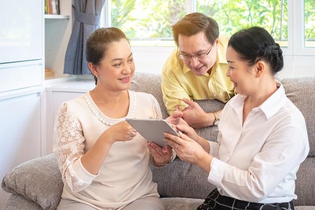 Aziatische hogere mensen, grootouders die digitale tablet in het huis gebruiken, gelukkige familie die technologieconcept gebruiken